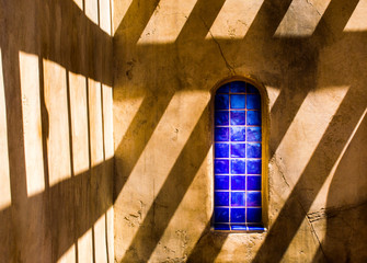 Spanish style arched blue tile window with shadow pattern