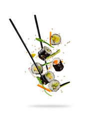Sushi pieces placed between chopsticks on white background