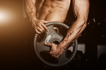 man in gym. Muscular bodybuilder guy doing exercises with barbell. Strong person with Tense strong male hand with veins barbell.Flare for text and design.