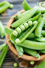 Pods sweet green peas in bowl closeup.