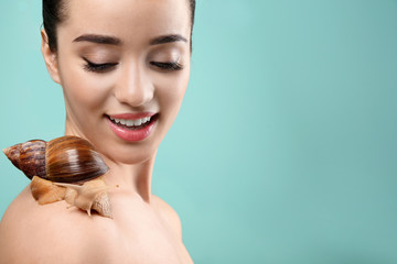 Beautiful young woman with giant Achatina snail on color background