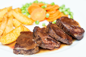 Juicy beef meat steaks with sauce, potatoes, carrots and peas on white plate, close-up. Selective focus