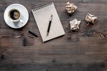 Writer concept. Coffee, vintage notebook and crumpled paper on wooden table background top view copyspace