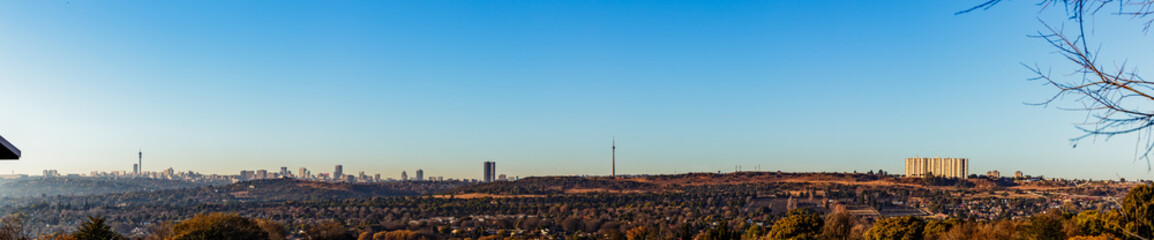 Wide Panorama view of Johannesburg City Skyline on a winter morning with mist low and clear skies