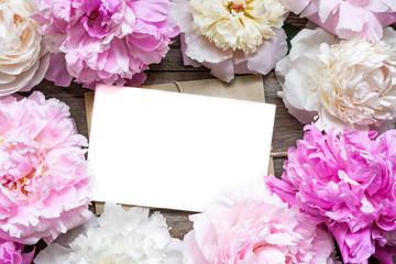 blank greeting card or wedding invitation and envelope in frame of tender peonies flowers