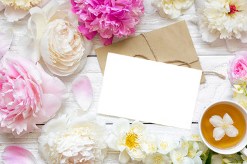 blank greeting card or wedding invitation with tender peonies and roses flowers with cup of green jasmine tea