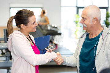 senior shaking hands with female trainer at gym