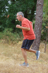 athletic mature man jogging in the forest
