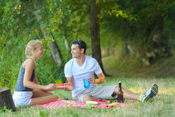 cute couple having picnic lying on a blanket