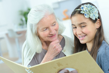young girl and grandmother watching photo album together