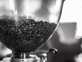 black and white picture of coffee beans in Coffee grinder, In a cafe.