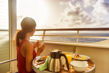 Wall Mural - Cruise ship luxury travel woman eating breakfast from room service on suite balcony enjoying morning view of Caribbean ocean. Summer sailing vacation lifestyle people drinking coffee.