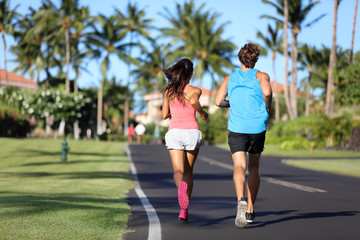 Runners athletes running training legs on road in residential neighborhood. Two people exercising together in summer city outdoors. Couple working out cardio.