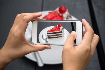 Taking photo of cake on wooden table.