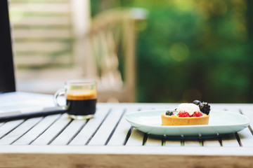 Desserts, coffee and laptop outside with a forest background