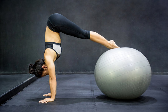 Young Asian athlete woman doing pilates exercises with exercise ball in fitness gym, healthy lifestyle concepts