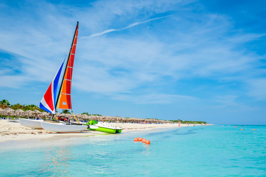 The tropical beach of Varadero in Cuba with a colorful sailboat