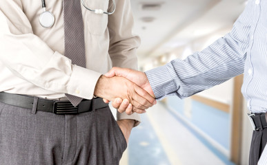 Doctors and businessman shaking hands
