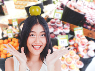 Beautiful woman holding apple on supermarket blurred background