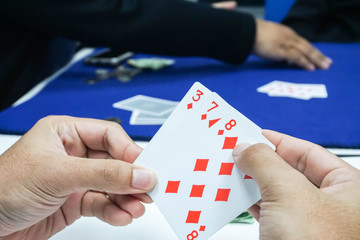 addiction concept - close up people play poker cards in hands for gambling