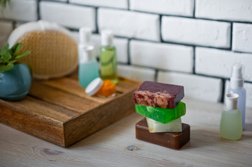 Bathroom accessories. Body care. Multi-colored natural soap, gels, shampoos, balms in vials, sea salt for a bath, a bast. Bathroom cosmetics on a light, white background. Spa treatments with candles