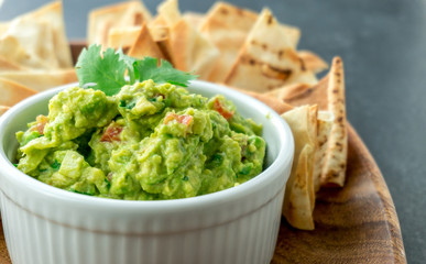 Guacamole close-up view. Guacamole is a avocado based dip, traditionally a mexican (Aztecs) dish. Healthy and easy to make at home with a few simple ingredients. Excellent as party food or at bars.