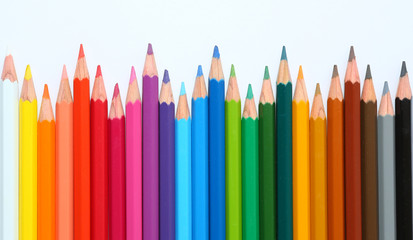 colored pencils row with wave on white background.
