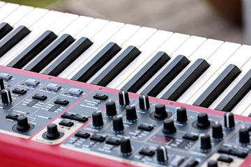 electronic synthesizer with keys, midi controller volume fader, knobs and sliders