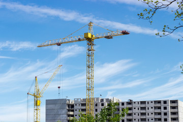 Two tower cranes against of multi-story residential building construction