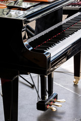 black grand piano with black and white keys on stage. closeup view.