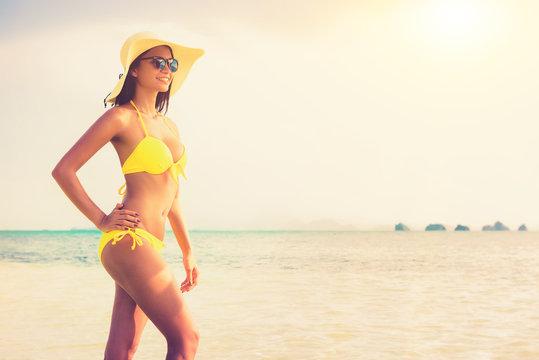 Asian woman wearing yellow bikini swimsuit, sunglasses and hat posing at the beach in summer