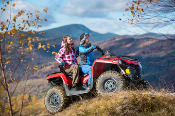 Happy women driving ATV on snowy hills in winter clothing on the background of mighty mountains and trees with yellow leaves. Sunny autumn day