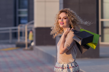 Beautiful woman turning around and smiling with shopping bags. happy girl with their purchases.