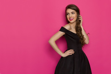 Smiling Elegant Woman In Black Dress Is Looking Away