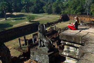 Young woman is sitting on the top of temple and she is looking on panorama of ancient ruins. Photographed in the temple complex of Angkor Wat, Cambodia