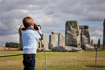 Young child, boy, taking pic with digital camera at Stonehenge