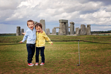 Two children, boy brothers, posing for the camera in front of Stonehenge in England