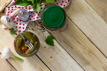 Marinated cucumbers gherkins. Marinated pickled cucumbers with red currant berries and spices on the kitchen wooden table. Top view with copy space.