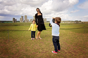Young child, boy, taking pic of his mom and brother with digital camera at Stonehenge