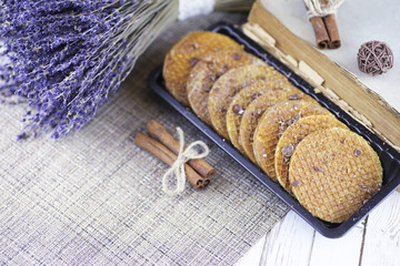Viennese wafers with caramel on a wooden background