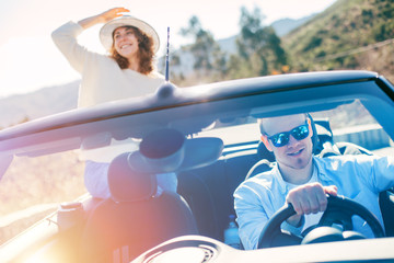 Young couple rejoices in the vacations and travels on a convertible