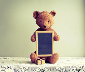 Old shabby toy bear with photo frame