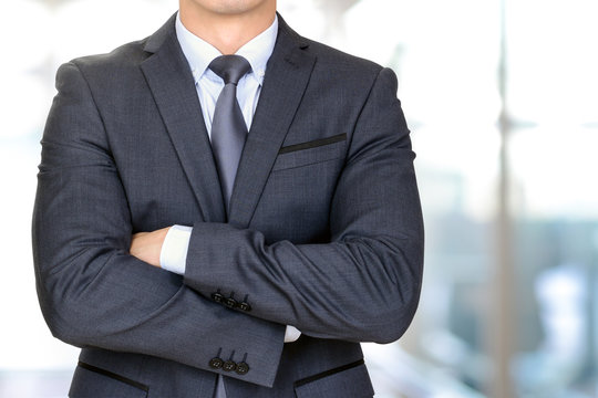 Anonymous businessman in dark gray suit crossing his arms