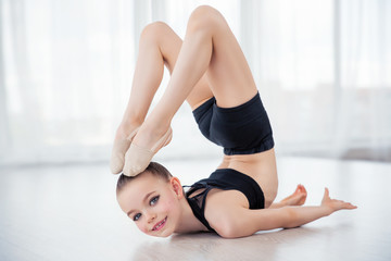Flexible child, beautiful little gymnast girl doing gymnastic exercises or exercising in fitness class