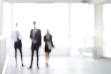 Blurred business people standing in white office building hall