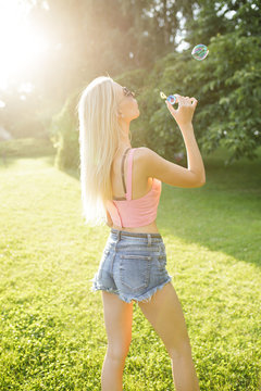 Pretty woman blowing bubbles in summer park