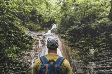 Traveler Has Reached Destination, Enjoying View Of Waterfall And Beauty The Unspoilt Nature. Contemplation Adventure Concept