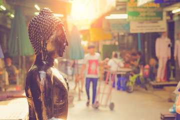 .Bangkok, Thailand - June, 21, 2017 : Black buddha statuse in amulet market and unidentified people walking inside for shopping