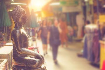 .Bangkok, Thailand - June, 21, 2017 : Black buddha statuse in amulet market and unidentified people walking inside for shopping