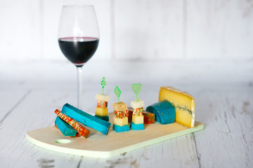 Plate with uncommon cheeses on a wood tray and glass of red wine